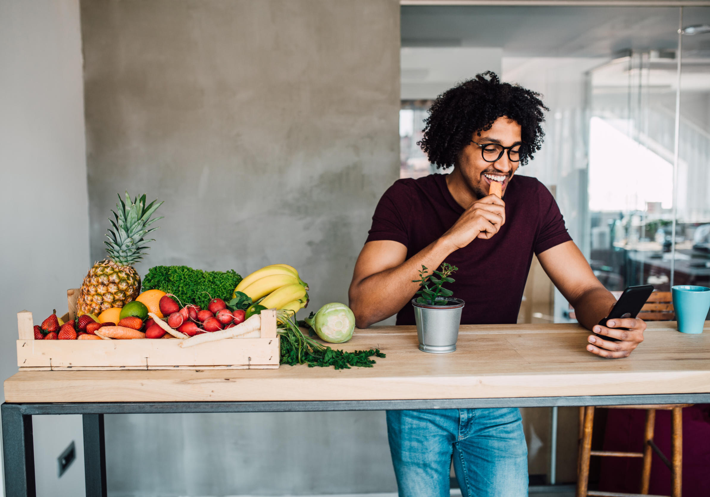 Young man having a healthy snack at home when using phone